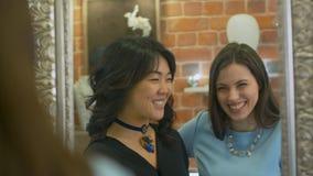 2 молодой женщины проверяя их взгляд и обсуждая новые приобретения в jewerly магазине Стоковое Фото