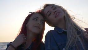 2 молодой женщины против захода солнца над морем лучи солнца светят между их головами сток-видео