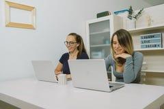 2 молодой женщины работая на компьтер-книжке на офисе Стоковые Фотографии RF