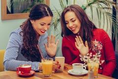 2 молодой женщины развевая рука и говоря пока имеющ видео- звонок с друзьями на смартфоне стоковое изображение