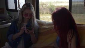 2 молодой женщины сидят на кресле в autotrailer окном со смартфонами в их руках сток-видео