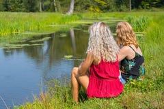 2 молодой женщины сидят совместно на портовом районе стоковая фотография rf