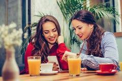 2 молодой женщины сидя на кафе, ослабляя и наблюдая что-то на умном телефоне стоковая фотография rf