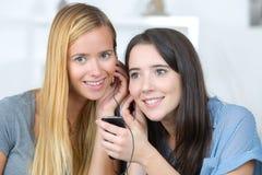 2 молодой женщины слушая такой же переговор стоковое фото rf