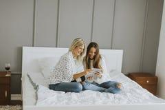 2 молодой женщины с таблеткой на кровати Стоковое фото RF