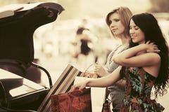 2 молодой женщины с хозяйственными сумками на автостоянке автомобиля Стоковая Фотография RF