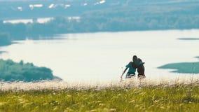 2 молодой женщины huging на поле в солнечном дне На предпосылке озера видеоматериал