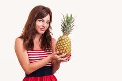 Молодой жизнерадостный усмехаться здоровая и радостная женщина с большим ананасом стоковая фотография