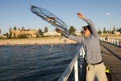 Молодой заход солнца дока сети корзины рыб и крабов счастливого и гордого привлекательного рыболова бросая на море в рыбной ловле Стоковая Фотография