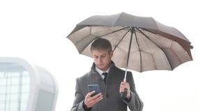 Молодой зонтик удерживания бизнесмена и использование умного телефона в a стоковые изображения rf