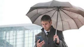 Молодой зонтик удерживания бизнесмена и использование умного телефона в a стоковые фото