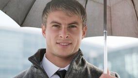 Молодой зонтик удерживания бизнесмена и использование умного телефона в a стоковые фотографии rf