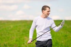 Молодой игрок в гольф рассматривает его гольф-клуб раньше Стоковое фото RF