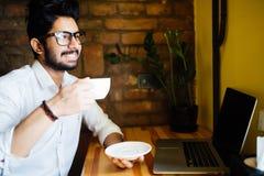 Молодой индийский бизнесмен используя компьютер во время перерыва офиса на кафе, ослабляя с чашкой кофе стоковые фотографии rf