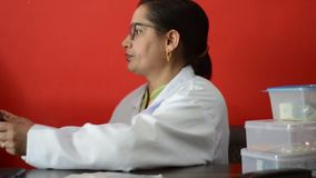 Молодой индийский доктор сидя в ее клинике сток-видео