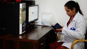 Молодой индийский доктор сидя в ее клинике акции видеоматериалы