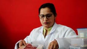 Молодой индийский доктор сидя в ее клинике видеоматериал