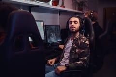 Молодой индийский парень нося военную рубашку сидя на стуле gamer и смотря камеру в клубе игры или стоковые фотографии rf