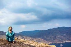 Молодой индийский человек на утесе скалы верхнего края холма выполняя йогу стоковые изображения rf