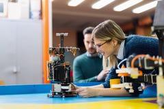 Молодой инженер испытывая ее робот в мастерской Стоковые Изображения RF
