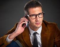 Молодой интересный бизнесмен говоря на телефоне Стоковые Изображения RF