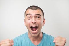Молодой испанский человек в голубой рубашке празднуя победу его команды над серой предпосылкой Стоковые Фото