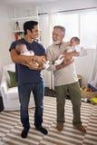 Молодой испанский человек и его старший отец держа его 2 ребенка дома, вертикальный стоковые фото