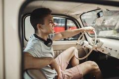 Молодой и привлекательный человек управляет винтажным автомобилем стоковое изображение