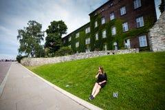 Молодой и счастливый турист женщины идя на замок Wawel в старом европейском городе Краков, Польше Перемещения вокруг Европы стоковые фотографии rf