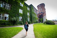 Молодой и счастливый турист женщины идя на замок Wawel в старом европейском городе Краков, Польше Перемещения вокруг Европы стоковое фото rf