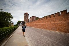 Молодой и счастливый турист женщины идя на замок Wawel в старом европейском городе Краков, Польше Перемещения вокруг Европы стоковые изображения rf