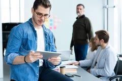 Молодой и творческий Красивый молодой человек держа цифровой планшет и усмехаясь пока его коллеги обсуждая что-то внутри стоковые фотографии rf