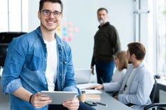Молодой и творческий Красивый молодой человек держа цифровой планшет и усмехаясь пока его коллеги обсуждая что-то внутри стоковое фото