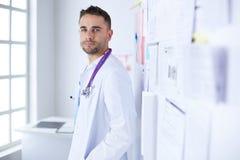 Молодой и уверенно мужской портрет доктора стоя в медицинском офисе Стоковое Изображение
