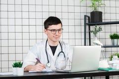 Молодой и усмехаясь терапевт в равномерной завалке вверх по документам стоковое фото
