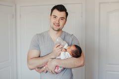 Молодой кавказский папа отца кормить newborn смешанной гонке азиатский китайский младенца стоковые изображения rf