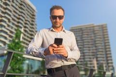 Молодой кавказский смартфон удерживания руководителя бизнеса для работы дела outdoors стоковые изображения rf