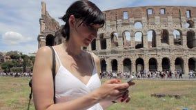 Молодой кавказский турист женщины отправляя СМС на красивом виде европейского древнего города с передвижным умным телефоном акции видеоматериалы