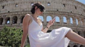 Молодой кавказский турист женщины отправляя СМС на красивом виде европейского древнего города с передвижным умным телефоном сток-видео
