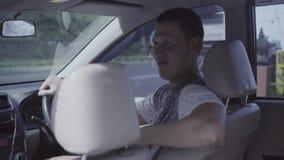 Молодой кавказский человек сидит в автомобиле, встряхивания возглавляют в рулевом колесе танца и поворотов сток-видео