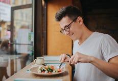 Молодой кавказский человек с стеклами есть здоровый салат стоковая фотография