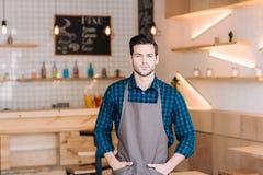 Молодой кельнер в кофейне стоковое изображение