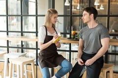 молодой кельнер и официантка имея переговор во время пролома на работе стоковые фото