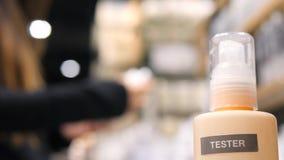 Молодой клиент женщины смешанной гонки выбирая сливк предохранения от солнцезащитного крема в супермаркете косметик в торговом це видеоматериал