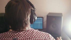 Молодой композитор парня составляет музыку на компьютере, деятельность звукооператора акции видеоматериалы