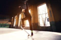 Молодой конькобежец в белой шляпе и черной фуфайке делает фокус с коньком скачет в покинутое здание в Стоковые Фото