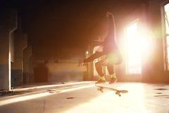 Молодой конькобежец в белой шляпе и черной фуфайке делает фокус с коньком скачет в покинутое здание в Стоковая Фотография