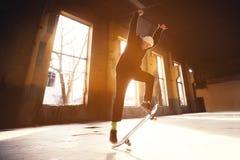 Молодой конькобежец в белой шляпе и черной фуфайке делает фокус с коньком скачет в покинутое здание в Стоковые Фотографии RF