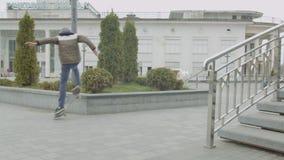 Молодой конькобежец делая фокус молотилки скейтборда outdoors
