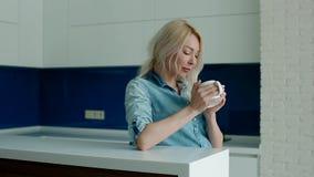 Молодой кофе белой женщины выпивая на современной кухне акции видеоматериалы